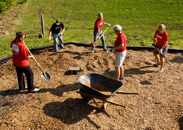 Volunteers from Keller Williams Realty Consultants of Southern Indiana spread mulch on a playground while volunteering for their company's Red Day at Greenville Park with help from the Floyd County Parks Department on Thursday morning. Staff photo by Christopher Fryer