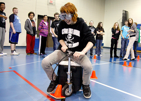C.J. Ponber, eighth-grader at Charlestown Middle School, tries to drive a motorized cart wearing drunk goggles during demonstations by Students Against Destructive Decisions on Tuesday. Along with drunken driving, students also tried out simulators for texting and driving. Staff photo by Jerod Clapp