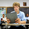 Junior Evan Hollkamp, 16, of Borden, uses an iPad during sacraments class on the first day of school at Providence Junior-Senior High School in Clarksville. All students were required to purchase the device for classes instead of paying a textbook rental fee. Staff photo by Christopher Fryer