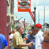 People mill around out front of Heuser Hardware Saturday afternoon eating and telling stories as the downtown Jeffersonville business celebrated its 90th anniversary. Staff photo by C.E. Branham