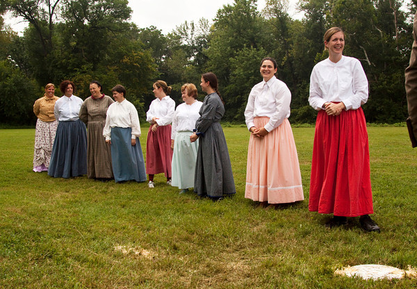 The Lady Diamonds, out of Columbus, Ohio, stand along the third base line during team introductions before their old fashioned baseball game against the New Albany Petunias at Binford Park in New Albany on Saturday. Staff photo by Christopher Fryer