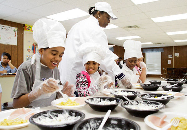 Davaughn Stovall, 10, left, and Makayla Williams, 5, both of New Albany, share a laugh as their instructor, Joyce Marshall, passes out their casserole dishes during the Little Chefs Cooking Class at the Beechwood Recreation Center in New Albany on Thursday afternoon. Staff photo by Christopher Fryer