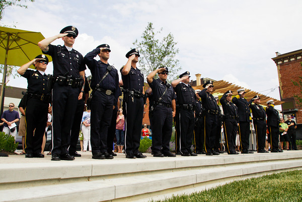 "New Albany police officers and firefighters salute the American Flag during the playing of ""The Star Spangled Banner"" at the official opening of the Bicentennial Park at the corner of Spring and Pearl streets in downtown New Albany on Friday evening. Staff photo by Christopher Fryer"