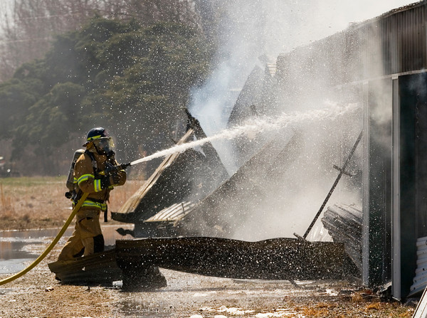 A firefighter works to contain a blaze at D&D Mini Storage, located along the 13000 block of U.S. 31, in Memphis on Tuesday afternoon. There was smoke damage to the entire 34 unit structure, and fire damage to 80 percent of the building. Staff photo by Christopher Fryer