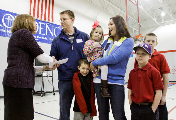 The Folz family accepts a check from Principal Terry Horton in the gymnasium of Our Lady of Perpetual Help Catholic School, where three of their four children are students, on Friday morning in New Albany. The family lost their home, located along Cliffwood Court, when it was destroyed by a fire last month on Valentine's Day. Along with the check, the school's community also collected gift cards, toys and household items for the family. The family are currently renting a house, and plan to rebuild their home on the same location. Staff photo by Christopher Fryer