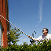 Rock Creek Community Academy junior Joseph Paro, 17, of Sellersburg, washes windows at Providence Retirement Home in New Albany on Friday afternoon. Paro, 17 other students and three teachers were cleaning at the home as part of the school's annual community service project, Helping Hands. Staff photo by Christopher Fryer