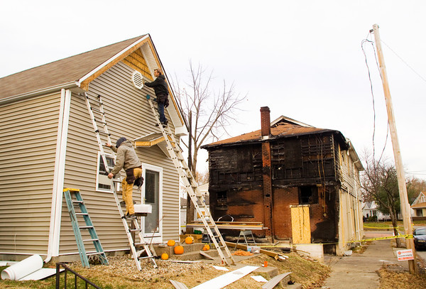 Dewayne Corn, Scottsburg, left, and Jeff Stotridge, New Albany, work on the siding of the house located at 2029 E. Oak St. in New Albany on Tuesday afternoon. The house was damaged when the two-story apartment building located at 601 Silver St., background, caught fire on October 31. Staff photo by Christopher Fryer