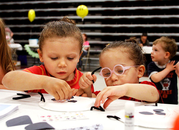 From left, Brianna Tharp, 4, and her sister Shirley, 3, piece together paper plate lady bugs at the Bright Futures Child Care booth at the Children's Academy of New Albany Early Childhood Fair on Friday morning. Around 25 booths were set up with information about various childhood services available in the area. Staff photo by Christopher Fryer