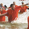 Clark County Sheriff's Department employees Mariah Alexander and Ryan Ooley make their way out of Deam Lake after participating in the 2012 Polar Plunge Saturday.  Staff photo by C.E. Branham