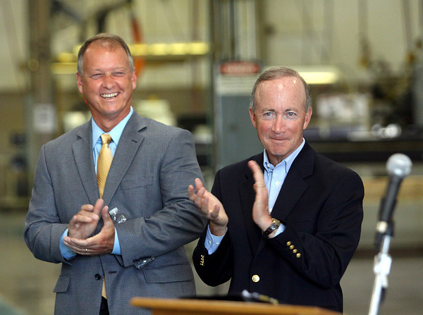 Indiana Gov. Mitch Daniels, right, and Jeffersonville Mayor Mike Moore applaud the announcement made by Advanced Metal Technologies, Inc., to invest $19 million dollars in its Jeffersonville plant at 100 Technology Way. Staff photo by C.E. Branham