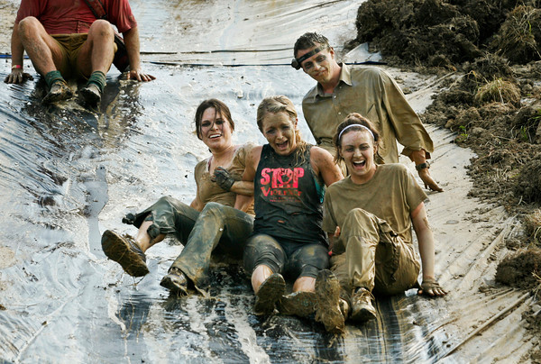 Members of team Who's Your Mudder? slide down an obstacle during the Muddy Fanatic 5K Adventure Race at the former Glenwood Training Center in Sellersburg on Saturday morning. Over 2000 participants negotiated over 30 obstacles on a 3.1 mile course either as individual racers or as part of a team. Staff photo by Christopher Fryer