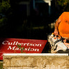 Joe Fitzmaurice, of Bloomington, uses a circular saw to take down the old Culbertson Mansion sign on the front lawn of the site along Main Street in downtown New Albany on Wednesday morning. The mansion is one of 11 historic sites across Indiana that are getting new signs. Staff photo by Christopher Fryer