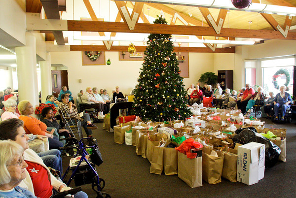 Gift bags sit beside a Christmas tree while residents wait to receive them at Yellowwood Terrace in Clarksville on Wednesday afternoon. About 120 gift bags were given out at the event through Home Instead Senior Care's Be A Santa To A Senior program. Staff photo by Christopher Fryer