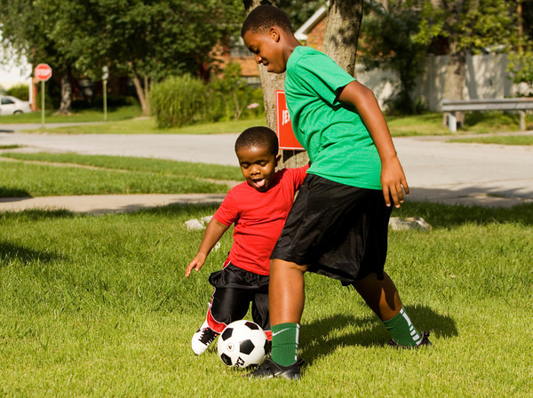 Amon Armour, 7, plays soccer with his cousin, Daon Alexander, 14, both of Jeffersonville, in front of his family's home on Thursday afternoon during a send off party to wish him well at this year's World Dwarf Games at Michigan State University. Armour was born with achondroplasia, which is a form of dwarfism. He will compete at the games in football, track and field, basketball, floor hockey, and soccer. Staff photo by Christopher Fryer