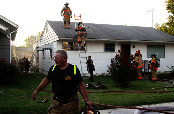 Members of the New Albany Fire Department work the scene of a fire they responded to at approximately 7:51 p.m. at the residence located at 2131 E. Market St. in New Albany on Wednesday evening. Nobody was injured during the fire. Staff photo by Christopher Fryer