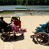 Wheel chairs sit on the shore as Camp Riley counselors assist campers in the swimming area of the lake at Indiana University's Bradford Woods near Martinsville on Tuesday morning. Staff photo by Christopher Fryer