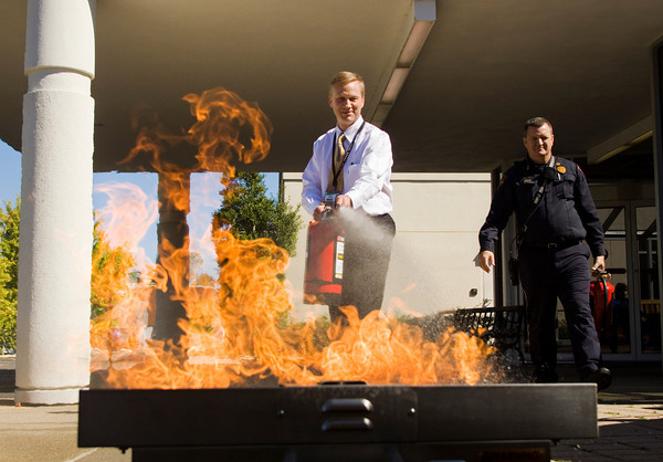 Vice President of Operations Mark Truman, New Albany, extinguishes flames in a fire extinguisher training prop during the first Floyd Memorial Hospital Safety Fair in New Albany on Tuesday afternoon. Local emergency agencies and vendors were set up at the fair designed to educate employees, patients and community members about home safety. Staff photo by Christopher Fryer