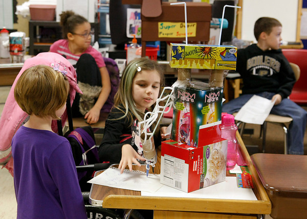 Shelby Fultz, a third-grader at Mount Tabor Elementary School, explains to a kindergartener what her robot, Writebot, does at the school's Robot Museum on Monday. Students had to explain the purpose of their robots to others. Staff photo by Jerod Clapp