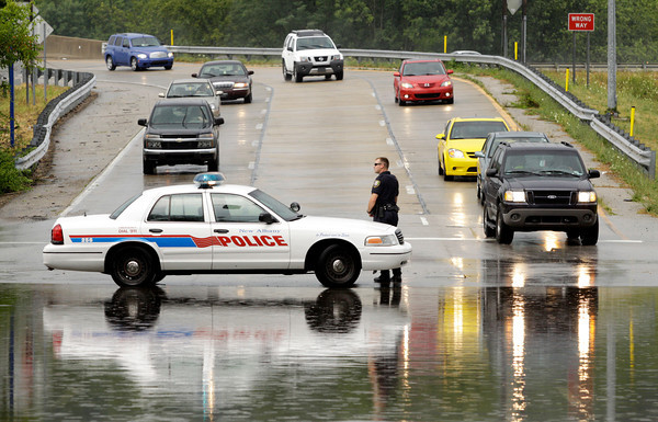 New Albany Police Department patrolman Cory Schneider uses his cruiser to keep traffic out of the flooded intersection of Scribner Drive and Elm Street in New Albany after a downpour on Sunday afternoon. Staff photo by Christopher Fryer
