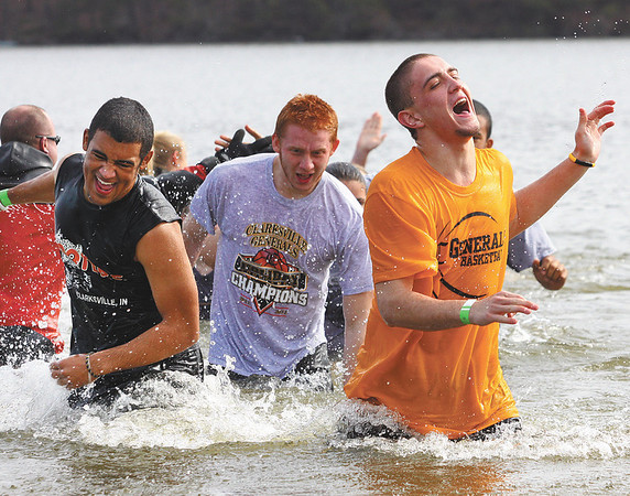Aidan McEwen, right, and other students from Clarksville High School hurry out of Deam Lake after taking the Polar Plunge on Saturday.  Staff photo by C.E. Branham