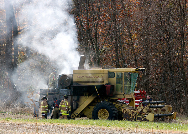 A combine caught fire around noon on Monday in a field off the intersection of Duffy Road and North Luther Road in Floyds Knobs. Georgetown and Lafayette Township fire departments responded with resources from Greenville Fire Department. Firefighters contained the blaze within five minutes and the operator was not injured. Staff photo by Jerod Clapp
