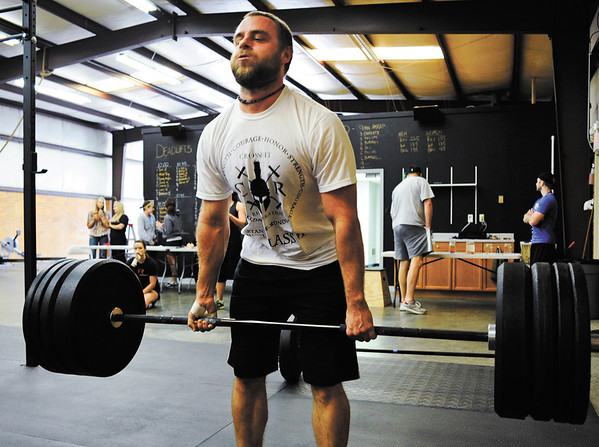 Charlie Sims, of Louisville, does a dead lift during a CrossFit competition at Clark Floyd CrossFit in New Albany on Saturday morning. Sims placed first in the men's competition and Rachel Kellington, of Louisville, placed first in the women's. The owner of the facility, Case Belcher, graduated from Henryville High School in 2005 and held the event to raise tornado relief funds for the school's athletic department. Staff photo by Christopher Fryer