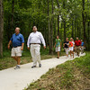 New Albany-Floyd County Parks Department Superintendent Roger Jeffers, left, and State Rep. Ed Clere walk through a section of the Campbell-Woodland Nature Trails after a dedication of the site on Thursday evening in Floyd County. Staff photo by Christopher Fryer