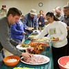 Community members from Henryville and the surrounding area fill their plates during a Thanksgiving dinner for victims of the March 2 tornadoes in the basement of St. Francis Xavier Catholic Church in Henryville on Thursday afternoon. Staff photo by Christopher Fryer