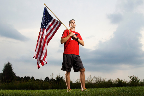 J.J. Pinter, 34, holds an American flag outside of his Palmyra home on Tuesday afternoon. Pinter, who served in the U.S. Army from 1997-2006, is the national director of operations, and runs the local chapter of Team Red, White and Blue, an agency that helps military veterans reintegrate back into society through physical fitness and community involvement. He and about 40 other runners are participating in A Moving Tribute today, where they will keep the flag moving around Louisville from sunrise to sunset in remembrance of Sept. 11. Staff photo by Christopher Fryer
