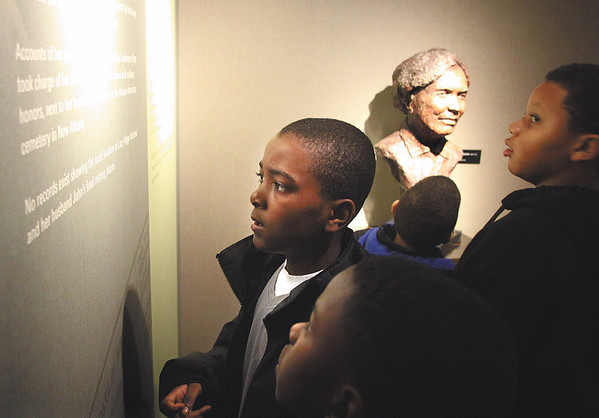 "Dashon Tyus and other members of Cub Scout Pack 994 from Louisville tour the new permanent exhibit, ""Remembered: The Life of Lucy Higgs Nichols,"" at the Carnegie Center for Art and History in New Albany.  The center hosted the grand opening Saturday.  Staff photo by C.E. Branham"