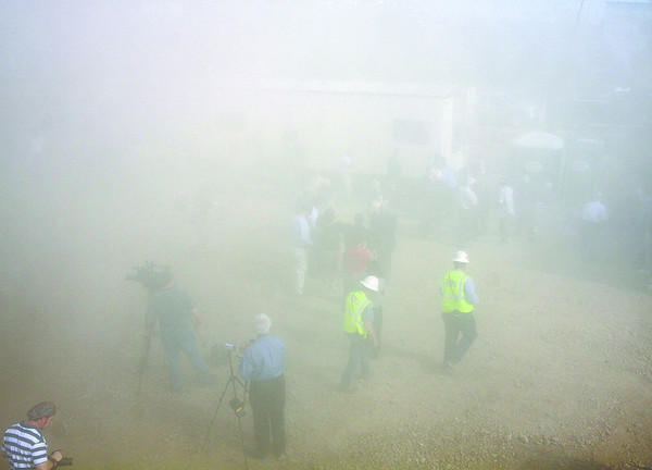 A dust cloud from a demolished smoke stack at River Ridge Commerce Denter envelopes spectators. Staff photo by C.E. Branham