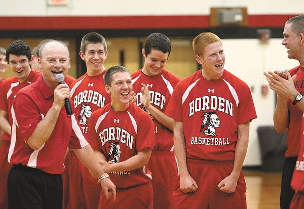 Members of the Borden High School basketball team enjoy comments by assistant coach Ray Weatherford, left, at a community pep rally Thursday night.  The Braves, 22-1, begin regional play Saturday morning in Loogootee.  Staff photo by C.E. Branham