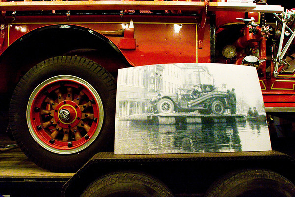 A historic photograph of the 1937 flood sits next to the restored 1921 American LaFrance fire truck that is featured in the photograph after it was unveiled during the fifth annual Vintage Fire Museum and Education Center chili cook-off at The Grand in downtown New Albany on Thursday evening. Staff photo by Christopher Fryer