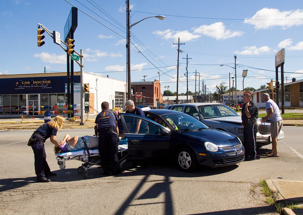 Emergency officials work the scene of a two-vehicle, injury accident at the intersection of Oak and State streets that occurred at about 11:35 a.m. on Friday morning in New Albany. The drivers were the only occupants of the vehicles, and the driver of the Dodge sedan, foreground, was taken to Floyd Memorial Hospital. Staff photo by Christopher Fryer