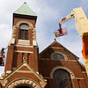 A crew with Schickel Masonry Restoration, out of Floyds Knobs, works on the exterior of St. John United Presbyterian Church along East Elm Street in New Albany on Thursday afternoon. They will be cleaning the entire exterior of the structure, as well as taking care of any brick and mortar repairs. Staff photo by Christopher Fryer
