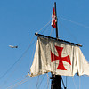 A jet liner flies overhead as a replica of the Christopher Columbus ship, the Pinta, sits docked on the Ohio River in downtown Louisville on Tuesday. Every three years replicas of the Niña and the Pinta are sailed from the Gulf of Mexico, up the East Coast, over to the Great Lakes, and through various waterways and rivers to eventually go up the Ohio River and end the journey in Pittsburgh. They are docked at various ports along the way for educational tours and will be open next to Joe's Crab Shack, 131 West River Rd., through September 4. Staff photo by Christopher Fryer