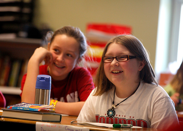 Hailee Craig, foreground, and Lily Jackey laugh during a lesson in their fifth grade class on Feb. 20 at Henryville Elementary School. Hailee said she lost a backpack with some personal effects in the tornado last year, but she misses sharing Goodfellas Pizza with her family. Staff photo by Jerod Clapp