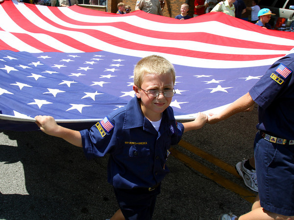 Members of Cub Scout Pack 48, Cub Scout Pack 49, and Boy Scout Troop 4010 carry a huge American flag down Spring St. in the city of Jeffersonville Celebrating Freedom Parade. Staff photo by C.E. Branham