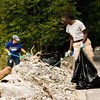 AmeriCorps National Civilian Commmunity Corps team member Aderonke Coker, Mt. Vernon, N.Y., right, and Indiana American Water volunteer Teresa Bierly, New Albany, pick up trash and debris scattered along Emery Crossing near the bridge over Mill Creek in Clarksville on Wednesday morning. Wednesday was the second of three days organized by AmeriCorps NCCC and the Ohio River Greenway Commission for cleanup and graffiti removal along the Ohio River in New Albany and Clarksville. Staff photo by Christopher Fryer