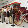 Board and committee members of the Vintage Fire Museum and Safety Education Center, 411 E. Spring St., stand with a late nineteenth century parade hose carriage in the New Albany museum on Tuesday afternoon. They are working to raise funds to purchase the building they are currently renting for the museum. Staff photo by Christopher Fryer