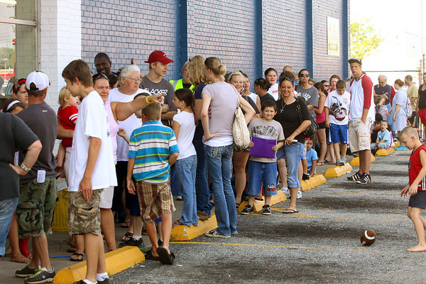 Hundreds of parents and children line up Wednesday morning outside the Salvation Army Thrift Store in Clarksville for the 22nd annual clothes giveaway. Staff photo by C.E. Branham