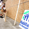AmeriCorps workers are building a storage facility to house supplies for the ten homes Habitat for Humanity will begin building in Henryville in October. Staff photo by C.E. Branham