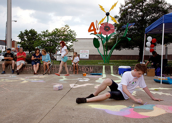 "Hunter Cooper, a senior at New Albany High School, draws on the sidewalk in front of R. Michael Wimmer's piece, ""Growth of Education"" during the New Albany Public Art Walk. Music, visual art and performances from the theater department at New Albany High School accompanied the public art pieces. Staff photo by Jerod Clapp"