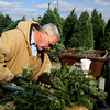 Kevin Arbuckle assembles a wreath at Martin's Christmas Trees in Jeffersonville. Martin's started making wreaths last year using scraps from their Frasier fir trees. Staff photo by C.E. Branham