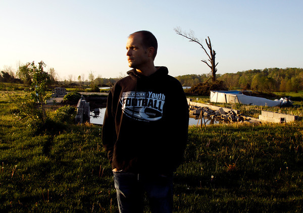 Darrell Gilles stands next to the ruins of his home on Friday morning in Henryville. Gilles and his family were taking shelter inside the house when it was lifted off the foundation and thrown several hundred yards during the March 2 tornadoes. Staff photo by Christopher Fryer