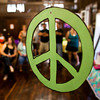 A peace sign hangs from the ceiling as attendants watch karaoke participants sing classic pop and rock tunes during the first Kids That Grew Up In The 60's and 70's In Clark County reunion at Lapping Park in Clarksville on Saturday afternoon. Staff photo by Christopher Fryer