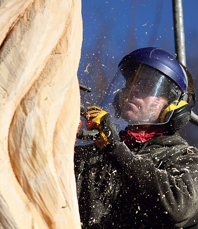 Autry uses a chain saw to shape his tree sculpture on Utica Pike.  Autry also sculpts ice, wood, metal and glass.  Staff photo by C.E. Branham