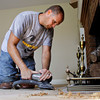 Darrell Gilles uses a sander while re-finishing a hardwood floor in a Louisville home on Tuesday morning. Gilles went back to work full-time in late June after recovering from injuries he received when his family's Henryville home was destroyed during the March 2 tornadoes. Staff photo by Christopher Fryer