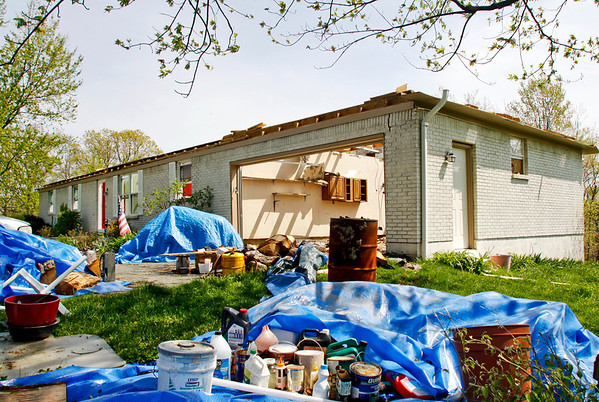 Salvaged items lay scattered in front of the home of Mike and Connie Scott in Borden on Friday afternoon. The home was hit during the March 2 tornadoes leaving the structure without a roof. Staff photo by Christopher Fryer