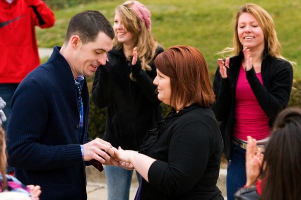 Gavin Catt presents his girlfriend Lauren Pepper with an engagement ring while proposing to her in front of the County Government Building, where she works as an administrative assistant, in Jeffersonville on Thursday morning. His proposal came after the Rainbow Dance Academy senior all stars staged a flash mob dance routine as she came outside the building. Staff photo by Christopher Fryer